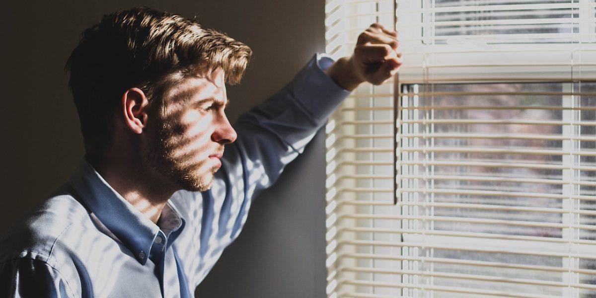 homme pensif regardant par la fenêtre