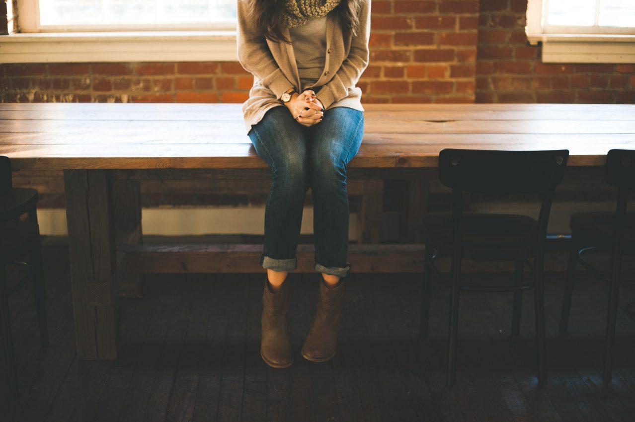 fille assise seule sur table de bois